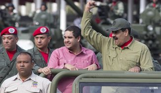 FILE - In this April 13, 2018 file photo, Nicolas Maduro Jr., center, accompanies his father, Venezuela's President Nicolas Maduro in a military parade, in Caracas, Venezuela. An action by the U.S. Treasury Department on Friday, June 28, 2019, freezes any U.S. assets belonging to Nicolas Maduro Jr. and prohibits American from doing business with him. (AP Photo/Ariana Cubillos, File)