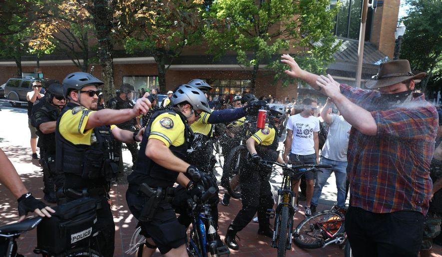 After a confrontation between authorities and protesters, police use pepper spray as multiple groups, including Rose City Antifa, the Proud Boys and others protest in downtown Portland, Ore., on Saturday, June 29, 2019. In separate social media posts later in the day, police declared the situation to be a civil disturbance and warned participants faced arrest. (Dave Killen/The Oregonian via AP)