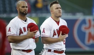 Los Angeles Angels' Albert Pujols, left, and Mike Trout listen to the national anthem before the team's baseball game against the Oakland Athletics on Friday, June 28, 2019, in Anaheim, Calif. (AP Photo/Marcio Jose Sanchez)