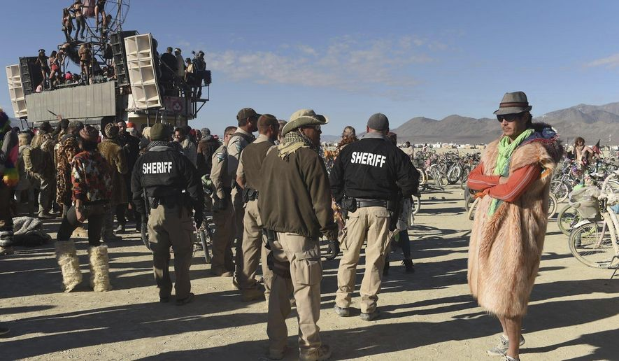 """FILE - In this Sept. 5, 2015, file photo, Sheriffs keep an eye on """"burners"""" at a party at Burning Man in the Black Rock Desert near Gerlach, Nev. Burning Man organizers say they won't challenge the U.S. Bureau of Land Management's plans to cap their attendance at current levels under a new 10-year permit but they will fight any move toward federally-sanctioned screenings for weapons and drugs at the counterculture celebration. BLM proposed earlier this month that private security firm be hired to screen all vehicles and participants. Burning Man says it would subject """"a peaceable gathering of people to searches without probable cause."""" (Andy Barron/Reno Gazette-Journal via AP, File)"""