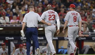 St. Louis Cardinals' Marcell Ozuna, center, leaves the field accompanied by a trainer and Mike Shildt during the third inning of a baseball game against the San Diego Padres, Friday, June 28, 2019, in San Diego. (AP Photo/Orlando Ramirez)
