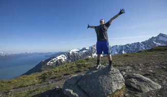 In this June 19, 2019 photo, Ben Schultz celebrates reaching the top of the Mt. Marathon race course in Seward, Alaska. Schultz, an Anchorage firefighter, fell from a ladder during a training accident in 2017 and is running the race as part of his recovery from the accident, which left him with a traumatic brain injury. Schultz climbed the steep, technical trail for the first time Wednesday with fellow firefighter and race veteran Rob Whitney. (Loren Holmes/Anchorage Daily News via AP)