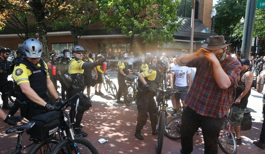 After a confrontation between authorities and protestors, police use pepper spray as multiple groups, including Rose City Antifa, the Proud Boys and others protest in downtown Portland, Ore., on Saturday, June 29, 2019. In social media posts later in the day, police declared the situation to be a civil disturbance and warned participants faced arrest. (Dave Killen/The Oregonian via AP)