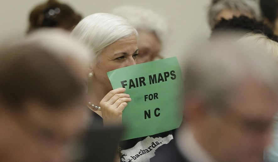 In this photo taken Wednesday, July 26, 2017 a member of the gallery tries to display her sign while lawmakers convene during a joint select committee meeting on redistricting in Raleigh, N.C. North Carolina's nearly continuous legal battles this decade over how maps for state district boundaries are drawn don't end with a landmark U.S. Supreme Court decision refusing to try to recalibrate boundaries to repair aggrieved political imbalances. (AP Photo/Gerry Broome)