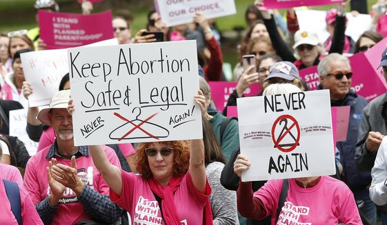 """In this May 21, 2019, file photo, people gather at the state Capitol to rally in support of abortion rights in Sacramento, Calif. The Trump administration has agreed to postpone implementing a rule allowing medical workers to decline performing abortions or other treatments on moral or religious grounds while the so-called """"conscience"""" rule is challenged in a California court. The rule was supposed to take effect on July 22, but the government and its opponents in a California lawsuit mutually agreed Friday, June 28, 2019, to delay a final ruling on the matter for four months. (AP Photo/Rich Pedroncelli, File)"""
