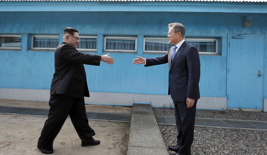 FILE - In this April 27, 2018, file photo, North Korean leader Kim Jong Un, left, prepares to shake hands with South Korean President Moon Jae-in over the military demarcation line at the border village of Panmunjom in Demilitarized Zone. U.S. President Donald Trump is inviting North Korea's Kim Jong Un to shake hands during a visit to the demilitarized zone with South Korea. Trump is scheduled to visit South Korea later Saturday after meetings at the Group of 20 summit in Osaka, Japan. (Korea Summit Press Pool via AP, File)