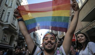 An activist brandishes a rainbow flag as Turkey's lesbian, gay, bisexual, trans and intersex activists march despite a ban, in Istanbul, Sunday, July 1, 2018.  The Istanbul LGBTI+ activists gathered in the city's Taksim neighbourhood after they announced Istanbul's local government had banned the Pride march for the fourth year in a row. (AP Photo/Emrah Gurel)