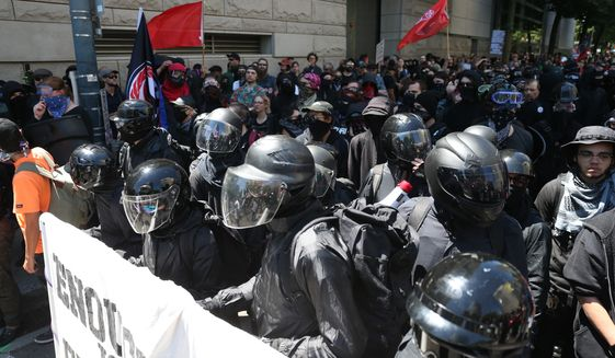In this file photo, protesters including Rose City Antifa, are shown in downtown Portland, Ore., Saturday, June 29, 2019. (Dave Killen/The Oregonian via AP) **FILE**