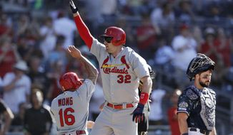 St. Louis Cardinals' Matt Wieters, center, celebrates with teammate Kolten Wong, left, after hitting a two-run home run as San Diego Padres catcher Austin Hedges looks on during the eleventh inning of a baseball game Sunday, June 30, 2019, in San Diego. (AP Photo/Gregory Bull)