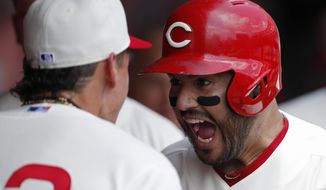 Cincinnati Reds' Eugenio Suarez, right, reacts in the dugout following a three-run home run off Chicago Cubs starting pitcher Jon Lester during the first inning of a baseball game, Sunday, June 30, 2019, in Cincinnati. Reds Derek Dietrich, left, looks on. (AP Photo/Gary Landers)