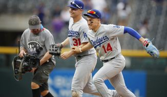Videographer Jim Hucks, left, tries to keep up with Los Angeles Dodgers left fielder Joc Pederson, center, and center fielder Enrique Hernandez as they race after a baseball game against the Colorado Rockies, Sunday, June 30, 2019, in Denver. (AP Photo/David Zalubowski)