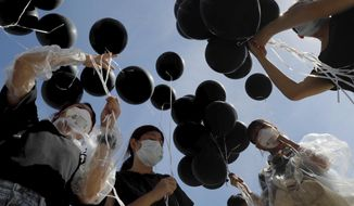Protestors hold black balloons to symbolize mourning for Hong Kong during protests in Hong Kong on Monday, July 1, 2019. The Hong Kong government marked the 22nd anniversary of the former British colony's return to China on Monday, as police faced off with protesters outside the venue. (AP Photo/Kin Cheung)