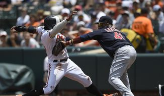 Baltimore Orioles' Dwight Smith Jr., left, is tagged out by Cleveland Indians first baseman Carlos Santana (41) on a pickoff play during the first inning of a baseball game, Sunday, June 30, 2019, in Baltimore. (AP Photo/Nick Wass)