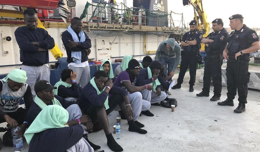 Migrants sit on the quay after disembarking at Lampedusa harbor, Italy, Saturday, June 29, 2019. Forty migrants have disembarked on a tiny Italian island after the captain of the German aid ship which rescued them docked without permission. Sea-Watch 3 rammed an Italian border police motorboat as it steered toward the pier on Lampedusa. (AP Photo/Annalisa Camilli)