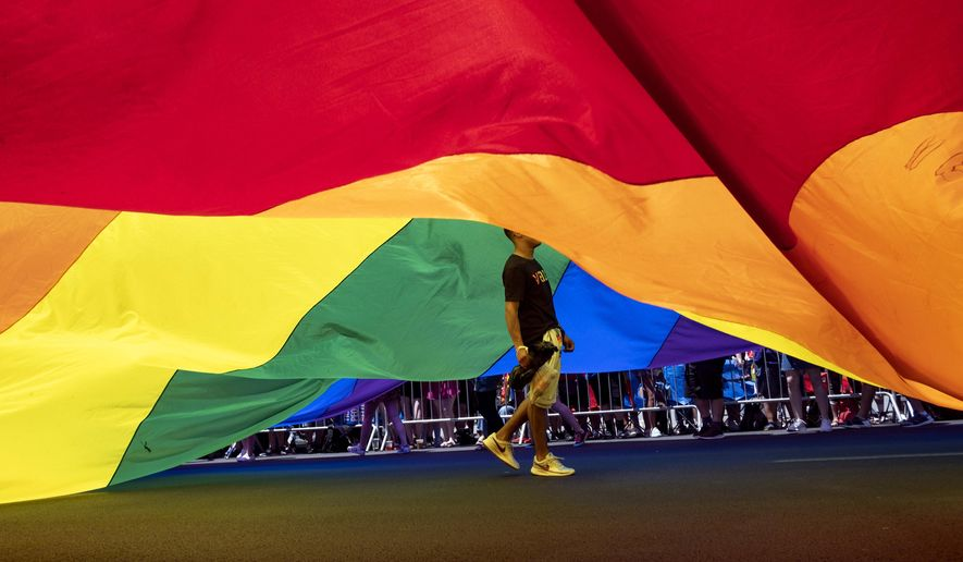 A participant walks under a large rainbow flag during the LBGTQ Pride march Sunday, June 30, 2019, in New York. (AP Photo/Craig Ruttle)