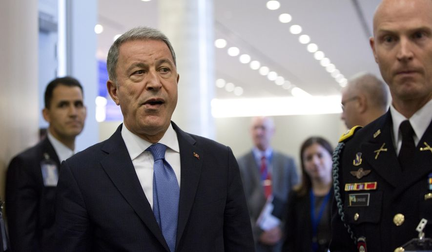 """FILE - In this Wednesday, June 26, 2019 file photo, Turkish Defense Minister Hulusi Akar, center left, arrives to NATO headquarters in Brussels. Turkey's defense ministry has said it is ready to retaliate against any attacks on Turkish vessels and interests by the forces of Libya's Khalifa Hifter. Akar said Sunday, June 30, 2019, that there would be """"heavy"""" consequences to any """"hostile attitude or attacks."""" (AP Photo/Virginia Mayo, Pool, File)"""