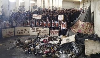 In this May 21, 2019 photo provided by an African migrant, hundreds of migrants stage a protest in a detention center in the town of Zintan, western Libya, appealing for help from the United Nations. In the desert of western Libya, hundreds of African migrants were held for months in a detention center, packed in amid garbage covered in maggots and sewage, shared buckets of water, and barely surviving on only one meal a day. More than 20 have died from disease and hunger, while EU-funded aid agencies had little knowledge of the situation, according to leaked memos and migrants. (AP Photo)