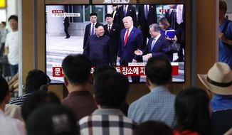 People in Seoul watched a TV screen Sunday showing President Trump, North Korean leader Kim Jong-un and South Korean President Moon Jae-in at the border villages of Panmunjom. (Associated Press)