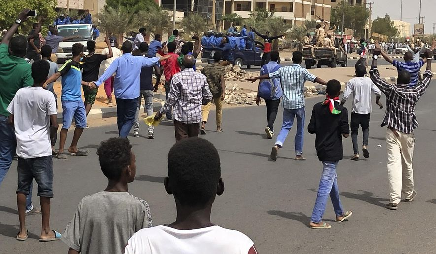 Sudanese protesters shout slogans as they block the road in front of riot police and an army convoy, during a demonstration against the military council, in Khartoum, Sudan, Sunday, June 30, 2019. Tens of thousands of protesters have taken to the streets in Sudan's capital and elsewhere in the country calling for civilian rule nearly three months after the army forced out long-ruling autocrat Omar al-Bashir. (AP Photo/Hussein Malla)