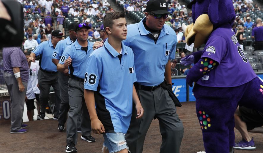 Thirteen-year-old Josh Cordova, left, of Denver, heads on the diamond with home plate umpire Cory Blaser before the Colorado Rockies host the Los Angeles Dodgers in the first inning of a baseball game Sunday, June 30, 2019, in Denver. The young man was officiating a youth baseball game when a brawl broke out among adults in the nearby suburb of Lakewood, Colo. (AP Photo/David Zalubowski) ** FILE **