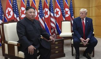 President Donald Trump, right, listens as North Korean leader Kim Jong Un, left, speaks during their bilateral meeting inside the Freedom House at the border village of Panmunjom in the Demilitarized Zone, South Korea, Sunday, June 30, 2019. (AP Photo/Susan Walsh)