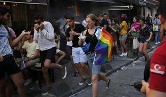 People run to avoid the effects of tear ga , fired by police to disperse activists on a street in central Istanbul, after a Pride march event was banned by authorities, in Istanbul, Sunday, June 30, 2019. Activists gathered in Istanbul to promote rights for gay and transgender people Sunday before police dispersed the crowd at a pride event that Turkish authorities had banned for the fifth year. (AP Photo/Lefteris Pitarakis)