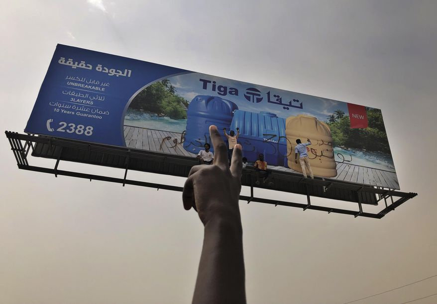 Sudanese protesters write graffiti on a billboard during a demonstration against the military council, in Khartoum, Sudan, Sunday, June 30, 2019. Tens of thousands of protesters have taken to the streets in Sudan's capital and elsewhere in the country calling for civilian rule nearly three months after the army forced out long-ruling autocrat Omar al-Bashir. The demonstrations came amid a weeks long standoff between the ruling military council and protest leaders. (AP Photo/Hussein Malla)