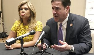 In this Friday, June 28, 2019 photo, Gov. Claudia Pavlovich of Sonora, Mexico, and Gov. Doug Ducey of Arizona talk to reporters in Phoenix. Ducey is a strong supporter of free trade and has fostered strong ties with Pavlovich, whose state borders Arizona, but he also consistently backs President Donald Trump's threats to shut down the border or unilaterally impose tariffs. Ducey's struggle to balance those positions was on display last week at a conference in Phoenix where he and Pavlovich commemorated the 60th anniversary of the Arizona Mexico Commission. (AP Photo/Jonathan J. Cooper)