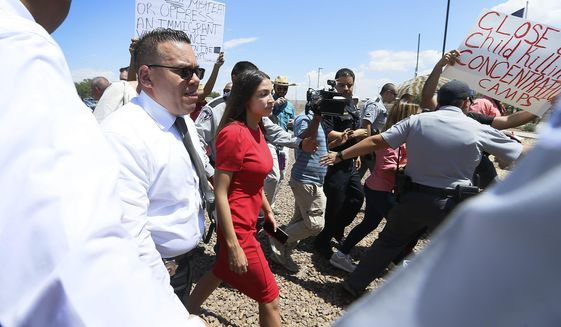 U.S. Rep. Alexandria Ocasio-Cortez, D-New York, is escorted back to her vehicle after she speaks at the Border Patrol station in Clint about what she saw at area border facilities Monday, July 1, at the station in Clint. (Briana Sanchez / El Paso Times via AP)