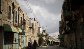 In this Wednesday, March 6, 2019, file photo, Palestinian women walk in a street where shops have been closed for a few years in the Israeli controlled part in the West Bank city of Hebron. The Falic family, owners of the ubiquitous chain of Duty Free America shops, fund a generous, and sometimes controversial, philanthropic empire in Israel that stretches deep into the West Bank. The family supports many mainstream causes as well as far right causes considered extreme even in Israel. (AP Photo/Ariel Schalit) ** FILE **