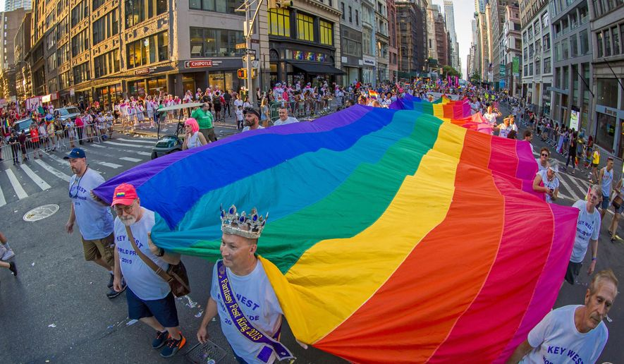 In this photo provided by the Florida Keys News Bureau, representatives from Key West, Fla., carry a 100-foot-long rainbow flag Sunday, June 30, 2019, during the LGBTQ Pride march in New York. (Jonathan Atkin/Florida Keys News Bureau via AP) ** FILE **