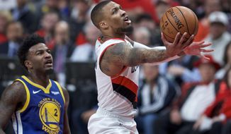 FILE - In this May 20, 2019, file photo, Portland Trail Blazers guard Damian Lillard, right, shoots near Golden State Warriors forward Jordan Bell during the first half of Game 4 of the NBA basketball playoffs Western Conference finals in Portland, Ore. (AP Photo/Craig Mitchelldyer, File)