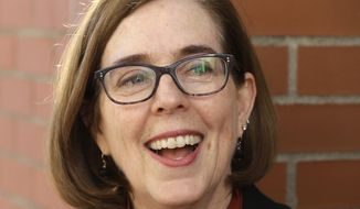 """In this Oct. 17, 2018 file photo, Oregon Gov. Kate Brown smiles during an interview in Portland, Ore. Gov. Brown says she's prepared to use her executive order privileges to lower carbon emissions herself if lawmakers can't find a compromise following a legislative session in which Republican state senators fled the state to thwart climate legislation. The governor said Monday, July 1, 2019 that she wants to move forward on a statewide cap and trade plan. The proposal caps carbon emissions and requires businesses to buy or trade an ever-dwindling pool of pollution credits or """"allowances."""" (AP Photo/Don Ryan, File)"""