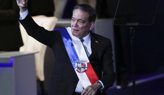 Panama's new President Laurentino Cortizo raises his fist after speaking during his inauguration in Panama City, Monday, July 1, 2019. Panama has sworn in for a five-year term the cattleman who inherits a slowing economy and growing frustration among Panamanians about official corruption. (AP Photo/Arnulfo Franco)