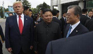 President Donald Trump, left, North Korean leader Kim Jong-un, center, and South Korean President Moon Jae-in, right, walk together at the border village of Panmunjom in Demilitarized Zone, South Korea, Sunday, June 30, 2019. (AP Photo/Susan Walsh)