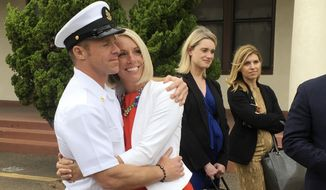 Navy Special Operations Chief Edward Gallagher, left, hugs his wife, Andrea Gallagher, after leaving a military courtroom on Naval Base San Diego, Thursday, May 30, 2019, in San Diego. The decorated Navy SEAL facing a murder trial in the death of an Islamic State prisoner was freed Thursday from custody after a military judge cited interference by prosecutors. (AP Photo/Julie Watson)