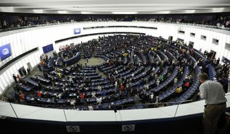 A man watches newly elected parliament members attending the new European Parliament first session in Strasbourg, eastern France, Tuesday July 2, 2019. EU voters turned out in numbers not seen in two decades for European Parliament elections in May, showing a renewed interest in the bloc's future after years marked by battles over Brexit and the continent's migrant crisis. (AP Photo/Jean-Francois Badias)