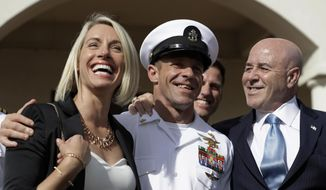 Navy Special Operations Chief Edward Gallagher, center, walks with his wife, Andrea Gallagher, left, and advisor, Bernard Kerik as they leave a military court on Naval Base San Diego, Tuesday, July 2, 2019, in San Diego. A military jury acquitted the decorated Navy SEAL Tuesday of murder in the killing of a wounded Islamic State captive under his care in Iraq in 2017. (AP Photo/Gregory Bull) **FILE**