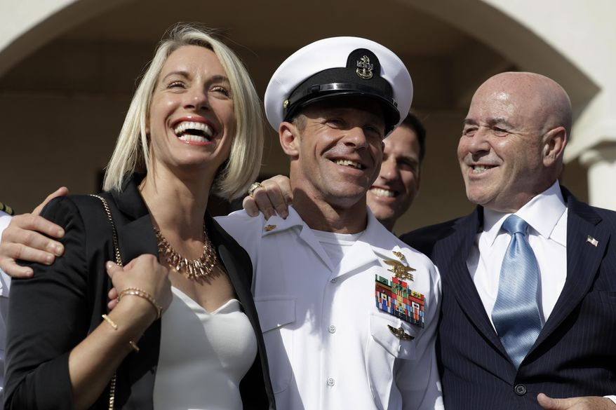 Navy Special Operations Chief Edward Gallagher, center, walks with his wife, Andrea Gallagher, left, and advisor, Bernard Kerik as they leave a military court on Naval Base San Diego, Tuesday, July 2, 2019, in San Diego. A military jury acquitted the decorated Navy SEAL Tuesday of murder in the killing of a wounded Islamic State captive under his care in Iraq in 2017. (AP Photo/Gregory Bull)