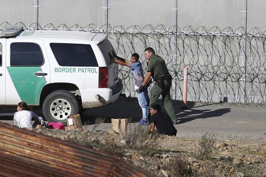 FILE - In this Dec. 15, 2018, file photo, Honduran asylum seekers are taken into custody by U.S. Border Patrol agents after the group crossed the U.S. border wall into San Diego, Calif., seen from Tijuana, Mexico. Immigrant rights activists on Friday, June 28, 2019, asked a U.S. judge to block a new Trump administration policy that would keep thousands of asylum seekers locked up while they pursue their cases, instead of giving them a chance to be released on bond.  (AP Photo/Moises Castillo, File)