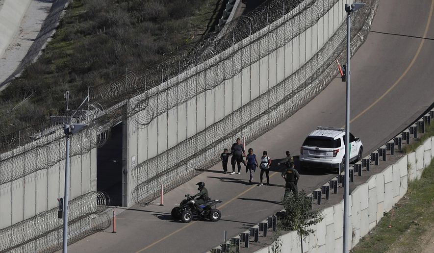 In this Dec. 16, 2018, file photo, Honduran asylum seekers are taken into custody by U.S. Border Patrol agents after the group crossed the U.S. border wall into San Diego, Calif., in this view from Tijuana, Mexico. (AP Photo/Moises Castillo, File)