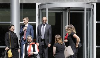 FILE - In this June 28, 2019, file photo, Matt Adams, center right, Legal Director of the Northwest Immigrant Rights Project, leaves the U.S. Courthouse with others after a hearing on asylum seekers in Seattle. On Tuesday, July 2, 2019, a federal judge in Seattle has blocked a Trump administration policy that would keep thousands of asylum seekers locked up while they pursue their cases. (AP Photo/Elaine Thompson, File)