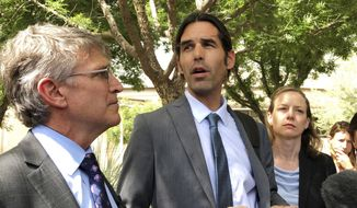 FILE - In this June 11, 2019 file photo Scott Warren, center, speaks outside federal court, in Tucson, Ariz., after a mistrial was declared in the federal case against him. Federal prosecutors are getting ready to announce whether they'll retry Warren, a border activist after a U.S. jury was unable to reach a verdict against him on charges of conspiracy to transport and harbor migrants. (AP Photo/Astrid Galvan,File)