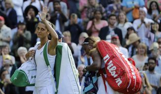Italy's Giulia Gatto-Monticone, left, waves as she leaves the court after losing to United States' Serena Williams, right, in a Women's singles match during day two of the Wimbledon Tennis Championships in London, Tuesday, July 2, 2019. (AP Photo/Ben Curtis)