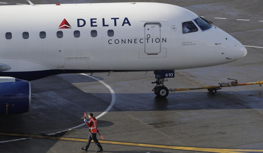 In this Feb. 5, 2019, file photo a ramp worker guides a Delta Air Lines plane at Seattle-Tacoma International Airport in Seattle. (AP Photo/Ted S. Warren, File)