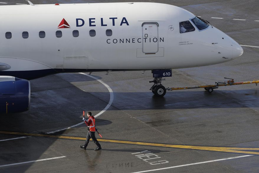 FIE - In this Feb. 5, 2019, file photo a ramp worker guides a Delta Air Lines plane at Seattle-Tacoma International Airport in Seattle. Delta Air Lines is boosting its forecast of second-quarter earnings per share because of rising revenue. The Atlanta-based airline said Tuesday, July 2, that it expects to earn between $2.25 and $2.35 per share for April through June. (AP Photo/Ted S. Warren, File)