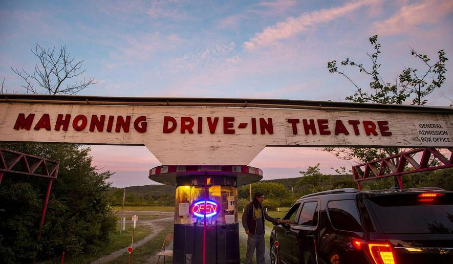 Mahoning Drive-in co-owner Matt McClanahan sells tickets on a recent Friday night. The theater is the last drive-in to show 35mm films every weekend. (April Gamiz/The Morning Call via AP)