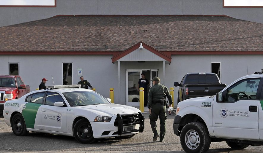 """In this June 23, 2018, photo, a U.S. Border Patrol Agent walks between vehicles outside the Central Processing Center in McAllen, Texas. A report released Tuesday, July 2, 2019, by the Department of Homeland Security's Office of Inspector General warns that facilities in South Texas' Rio Grande Valley, including the CPC in McAllen, face """"serious overcrowding"""" and require """"immediate attention.""""  (AP Photo/David J. Phillip) **FILE**"""
