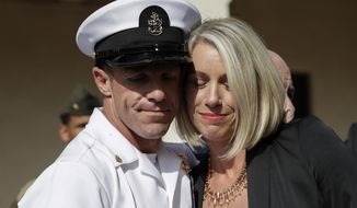 Navy Special Operations Chief Edward Gallagher, left, and his wife, Andrea Gallagher hug after leaving a military court on Naval Base San Diego, Tuesday, July 2, 2019, in San Diego. A military jury acquitted the decorated Navy SEAL Tuesday of murder in the killing of a wounded Islamic State captive under his care in Iraq in 2017. (AP Photo/Gregory Bull)