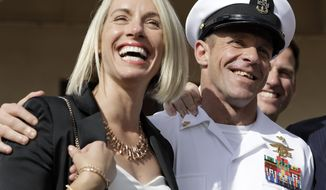 Navy Special Operations Chief Edward Gallagher, left, and his wife, Andrea Gallagher smile after leaving a military court on Naval Base San Diego, Tuesday, July 2, 2019, in San Diego. A military jury acquitted a decorated Navy SEAL of premeditated murder Tuesday in the killing of a wounded Islamic State captive under his care in Iraq in 2017. (AP Photo/Gregory Bull)